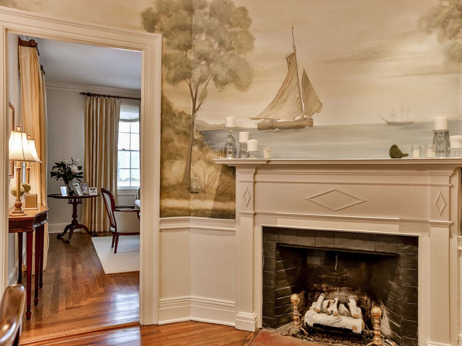 A nautical-inspired mural positioned above a fireplace tells a story and creates a design statement in this space. — William Raveis/Wendy Ryan photo / House Lens