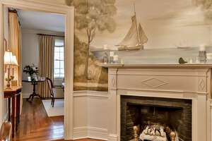 A nautical-inspired mural positioned above a fireplace tells a story and creates a design statement in this space. — William Raveis/Wendy Ryan photo