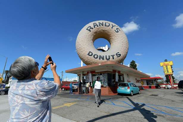 LOS ANGELES, CA - OCTOBER 10: A man takes a picture with his mobile phone of a toy space shuttle placed in the dounut hole of Randy's Donuts in preparation of the ground transport of the space shuttle Endeavour on October 10, 2012 in Los Angeles, California. The orbitor will stop in front of the donut shop for several hours to shoot a Toyota commercial. The space shuttle will start its trek from the Los Angeles International Airport to the California Science center on Friday. (Photo by Kevork Djansezian/Getty Images)