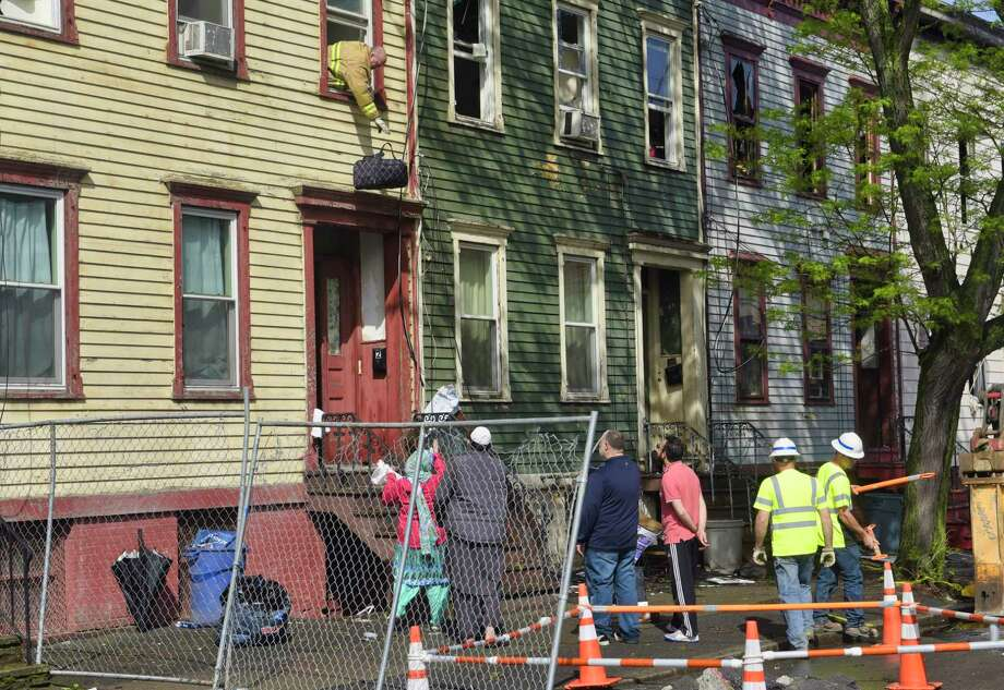 Dan Sherman, with the City of Albany Code Enforcement Department, drops a bag of clothes out of a window of one of the Bradford Street apartments damaged by fire on Monday, May 20, 2019, in Albany, N.Y. Sherman was retrieving some items for a family. An early morning fire on Sunday damaged several apartment buildings on Bradford Street.   (Paul Buckowski/Times Union) Photo: Paul Buckowski, Albany Times Union / (Paul Buckowski/Times Union)