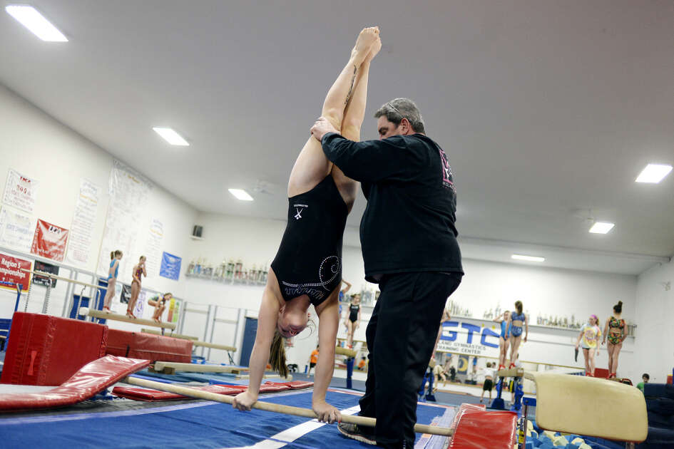 Gymnast Sammy Gouge works with MGTC owner/coach Jim Comiskey during practice on May 7, 2016.