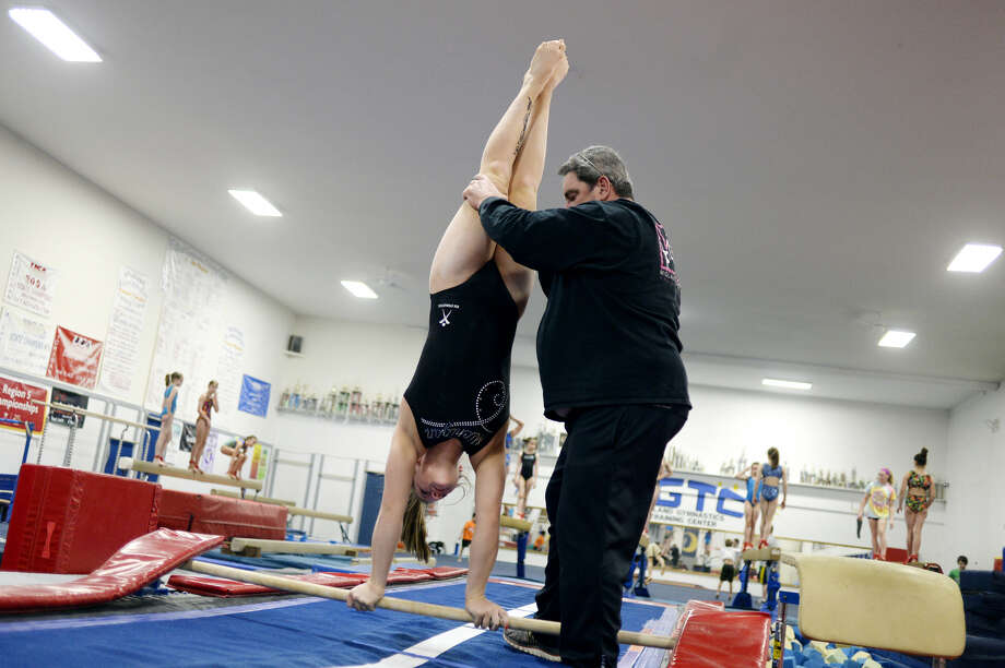 Gymnast Sammy Gouge works with MGTC owner/coach Jim Comiskey during practice on May 7, 2016. Photo: Daily News File Photo