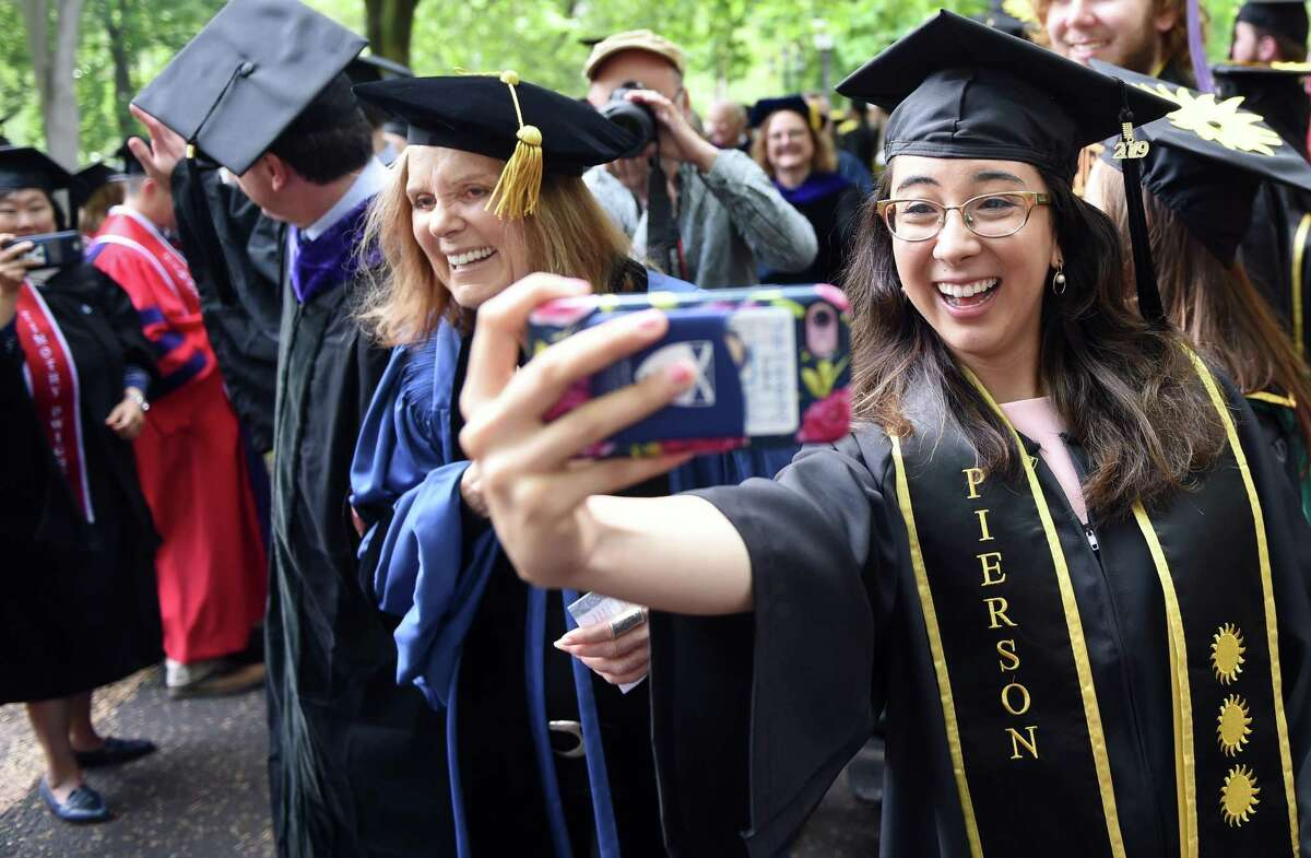 Valentina Guerrero (right) of Pierson College takes a selfie with honorary degree recipient Gloria Steinem (left) as the processional for Yale University's 318th Commencement winds through the Upper Green in New Haven on May 20, 2019.