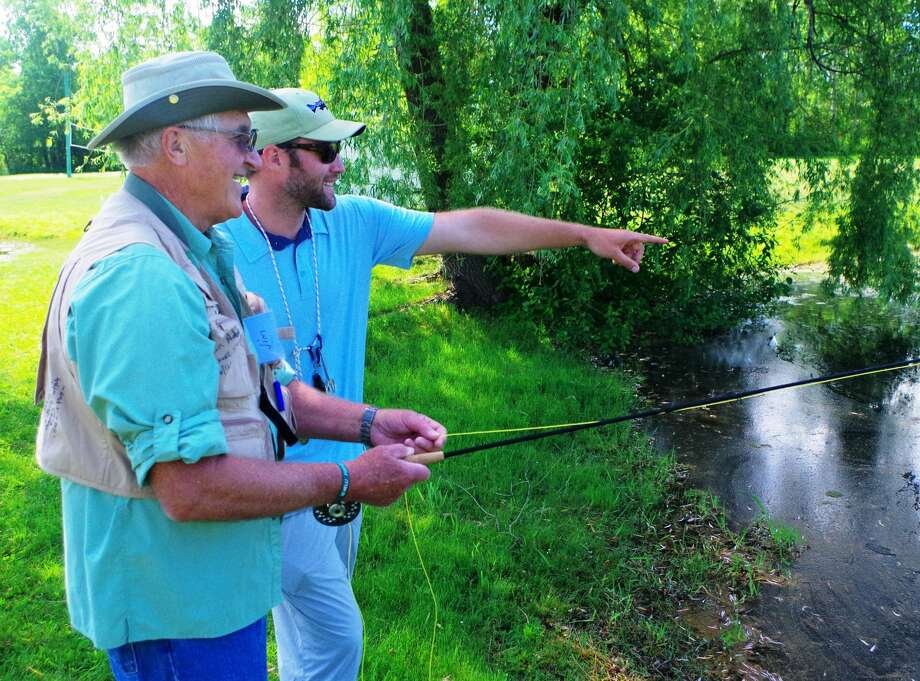Reel Recovery fishing buddy Trent Hartwig (right) points out a rising fish to participant Jim McKimmy, of Elk Rapids, at the Ranch Rudolf trout pond.  Photo: Patrick Bevier/for The Daily News