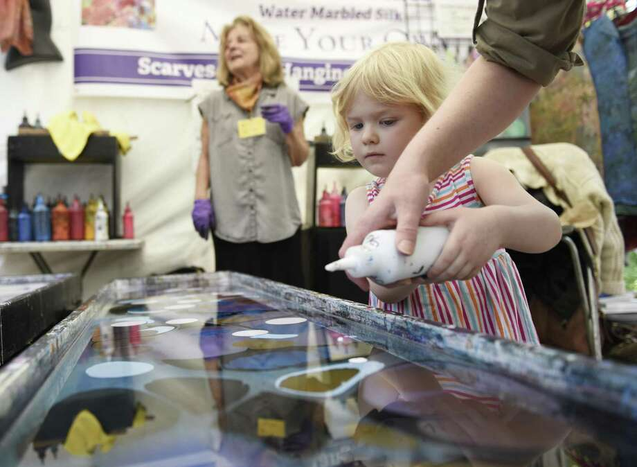 Cos Cob's Bailey Haberli, 4, creates a water-marbled silk at the Shibumi Silks stand at the 34th Annual Outdoor Crafts Festival at the Bruce Museum in Greenwich, Conn. Sunday, May 19, 2019. The two-day festival featured more than 70 exhibitors of crafts such as jewlery, weavings, sculptures, metalwork, clothing, ceramics, and more. The event featured live music, craft demonstrations, and several food trucks. Photo: Tyler Sizemore / Hearst Connecticut Media / Greenwich Time