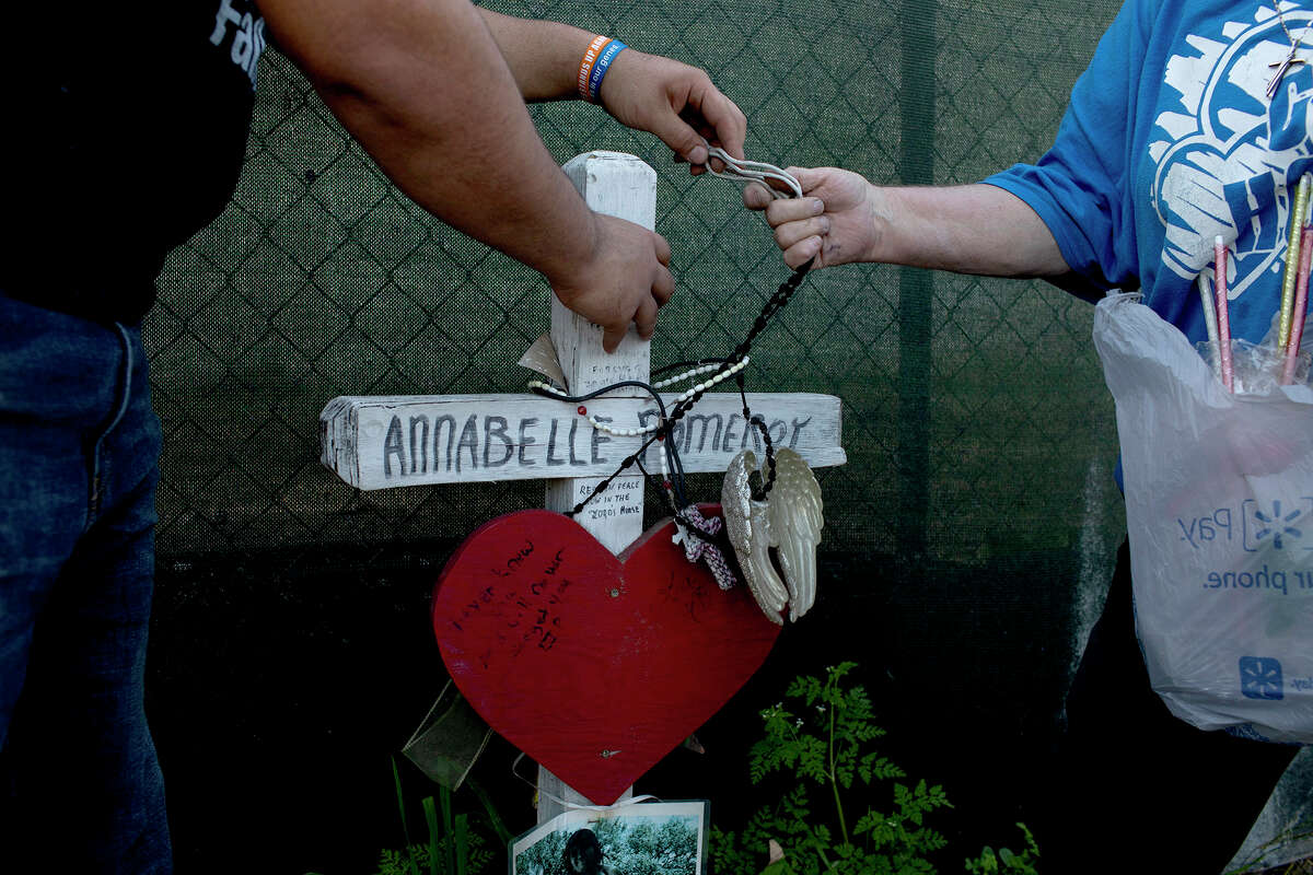 Mementos are removed from Annabelle Pomeroy's memorial cross to take the cross to the Sutherland Springs Historical Museum on Feb. 27, 2019. The memorial crosses were all removed from their place along U.S Highway 87 to make way for construction connected to the new building for First Baptist Church of Sutherland Springs.