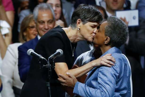 Lori Lightfoot, right, is kissed by wife Amy Eshleman after Lightfoot was sworn in as mayor at Wintrust Arena in Chicago on Monday, May 20, 2019. (Jose M. Osorio/Chicago Tribune/TNS)