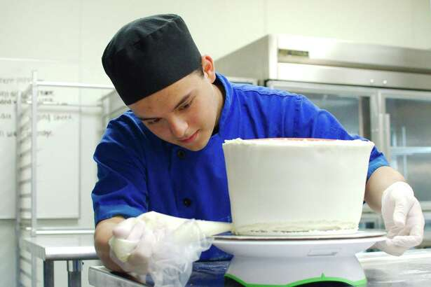 Friendswood Culinary Arts student Ruben Rubalcava spreads icing on a cake.