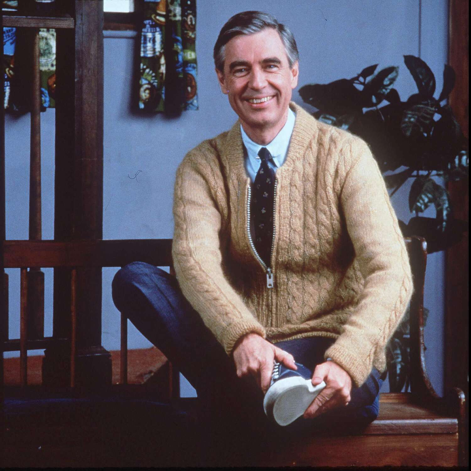 American TV personality Fred Rogers sits wearing a tan zip-up sweater over a shirt and tie with gray slacks.