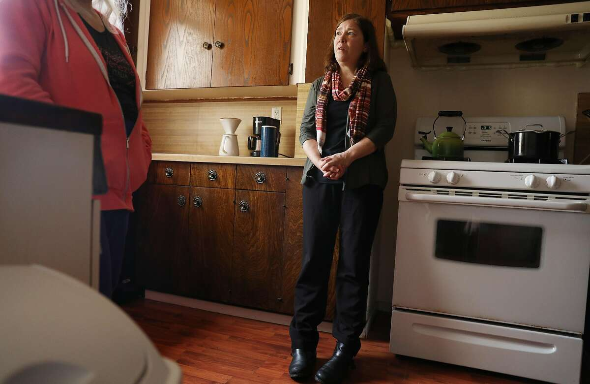 Chris Perry (right), Progress Foundation assistant director of supportive living programs, listens to resident Connie Weissman (left) speak as they stand in the kitchen at a Progress Foundation co-op in the Oceanview district on Monday, May 20, 2018 in San Francisco, Calif.