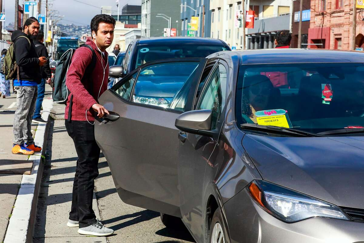 A man gets into a Lyft car outside the Cal Train station on Townsend Street in San Francisco, California, on Monday, May 20, 2019. Both Uber and Lyft have agreed to a 3.25%-per ride tax in an effort to avoid a tax on their gross receipts. The taxes will generate an estimated $30 million to $35 million for transportation improvements and street-safety upgrades.