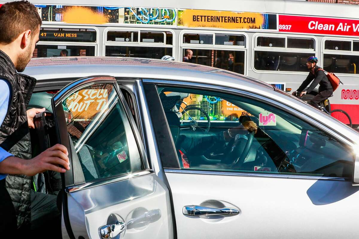 A man hops into a Lyft car outside the Cal Train station on Townsend Street in San Francisco, California, on Monday, May 20, 2019. Both Uber and Lyft have agreed to a 3.25%-per ride tax in an effort to avoid a tax on their gross receipts. The taxes will generate an estimated $30 million to $35 million for transportation improvements and street-safety upgrades.