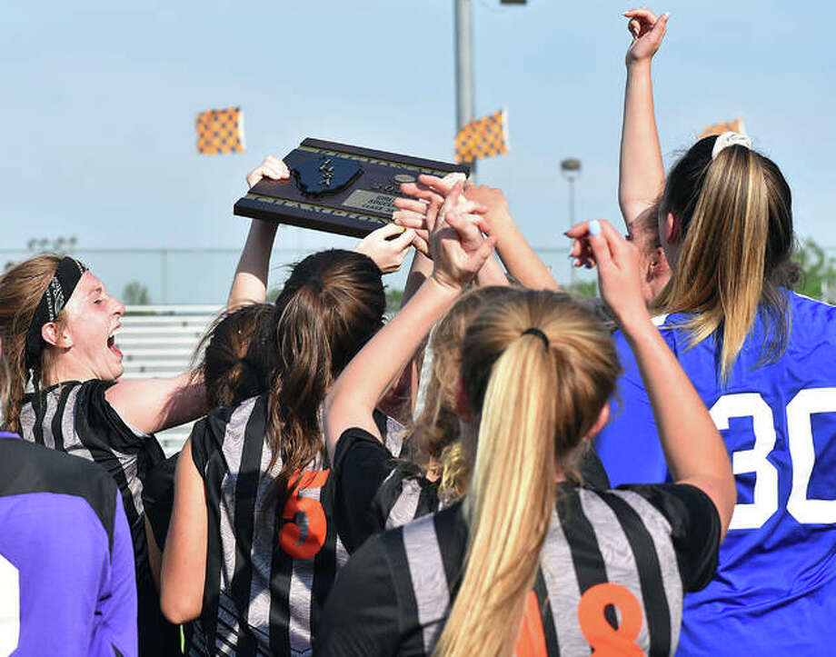 Members of the EHS girls soccer team celebrate with the Class 3A Edwardsville Regional championship plaque after defeating O'Fallon on Friday. Photo: Matt Kamp/The Intelligencer