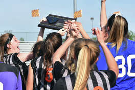 Members of the EHS girls soccer team celebrate with the Class 3A Edwardsville Regional championship plaque after defeating O'Fallon on Friday.