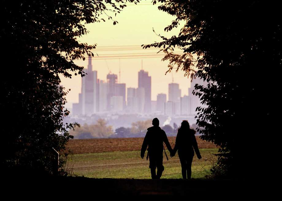 A couple walks through a forest in 2018 with the Frankfurt, Germany skyline in background. Development that's led to loss of habitat, climate change, overfishing, pollution and invasive species is causing a biodiversity crisis, scientists say in a new United Nations science report released recently. Photo: Michael Probst /Associated Press / Copyright 2018 The Associated Press. All rights reserved