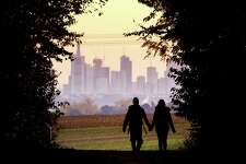 A couple walks through a forest in 2018 with the Frankfurt, Germany skyline in background. Development that's led to loss of habitat, climate change, overfishing, pollution and invasive species is causing a biodiversity crisis, scientists say in a new United Nations science report released recently.