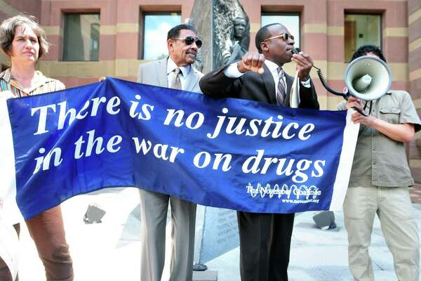 Activists speak at a protest about the War on Drugs in front of CIty Hall in New Haven, Connecticut in 2013. We've been losing this war for awhile - but maybe that's the point.