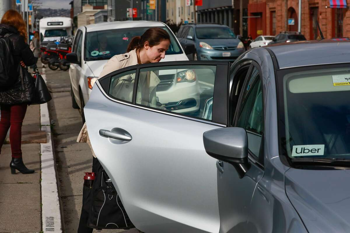 A woman hops into a Uber car outside the Cal Train station on Townsend Street in San Francisco, California, on Monday, May 20, 2019. Both Uber and Lyft have agreed to a 3.25%-per ride tax in an effort to avoid a tax on their gross receipts. The taxes will generate an estimated $30 million to $35 million for transportation improvements and street-safety upgrades.