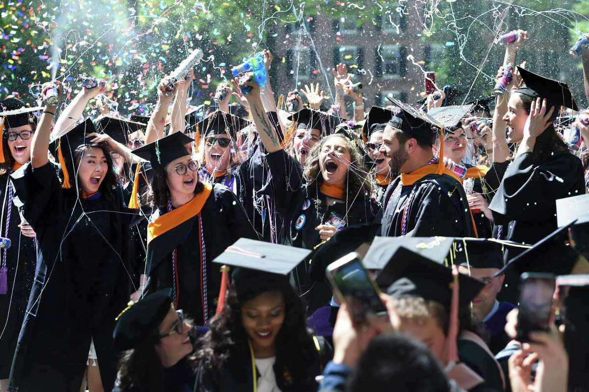 Graduates from the School of Nursing celebrate at Yale University's 318th Commencement on Old Campus in New Haven on Monday. Below,