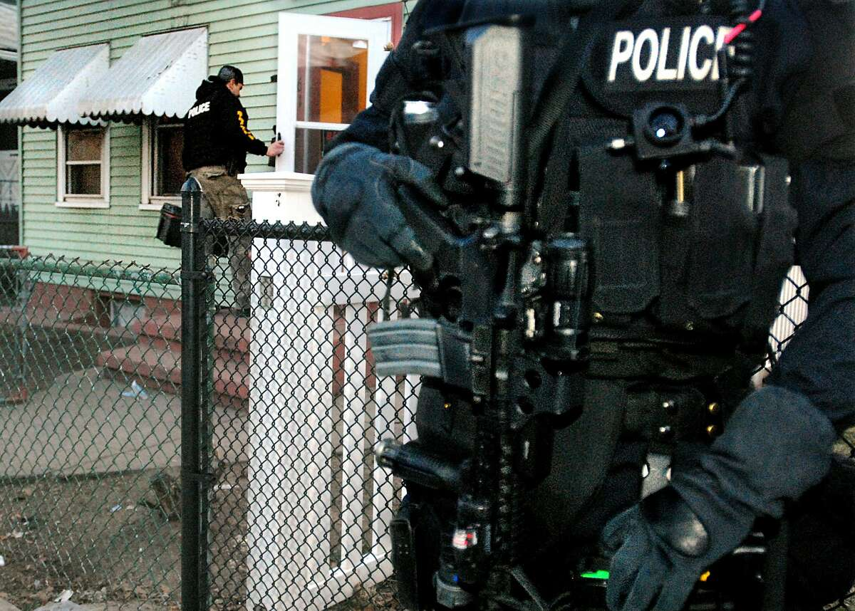 (ms021809)-Police search a house on Liberty Street in New Haven. In the forground is a member of the S.W.A.T. team. A drug arrest was made at this location. Melanie Stengel/Register