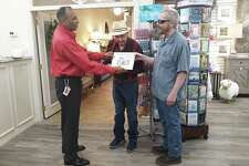 Hari Kotaiya, with the Plainview Chamber of Commerce, hands Jack Oswald and Larry Hinds a symbolic first dollar after a ribbon cutting to showcase the Haven's renovations and rebranding Thursday.