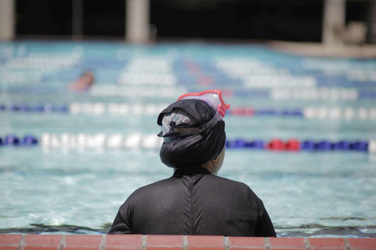 Zainab Altameemi takes a break from swimming laps during practice at Trotter Family YMCA with the assistance of Interfaith Ministries on Monday, April 22, 2019 in Houston.