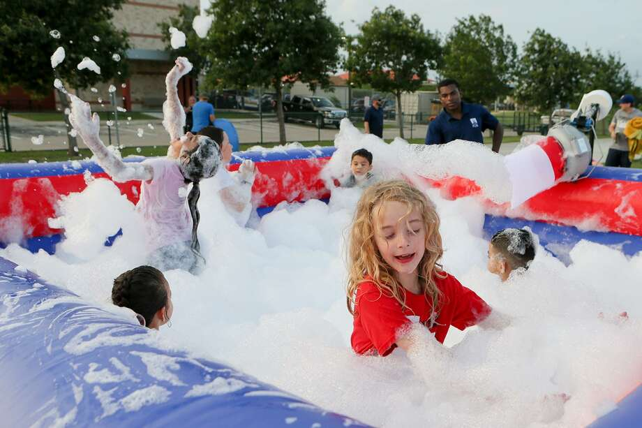 Sara Turner, front right, plays with other children in a foam and bubble-filled bounce house during Cibolo Summer Nights at the Cibolo Multi-Event Center on Friday. The event was this year's kickoff of the Cibolo Summer Nights, a free community-centered program that includes family-friendly activities and movie screenings. Photo: Marvin Pfeiffer /Staff Photographer / Express-News 2019