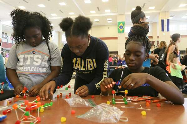 Cenilyn Green, 13, from right, Kortlyn Sayles, 13, and Quinlyn Green, 10, attempt to design load bearing structures using the least amount of materials in a civil engineering experiment at the Valero booth during STEM Day at Wagner High School on Saturday.