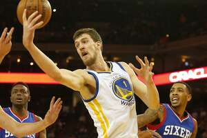 Golden State Warriors center Ognjen Kuzmic reaches for a rebound during the fourth quarter of the basketball game on Tuesday, December 30, 2014 in Oakland, Calif.