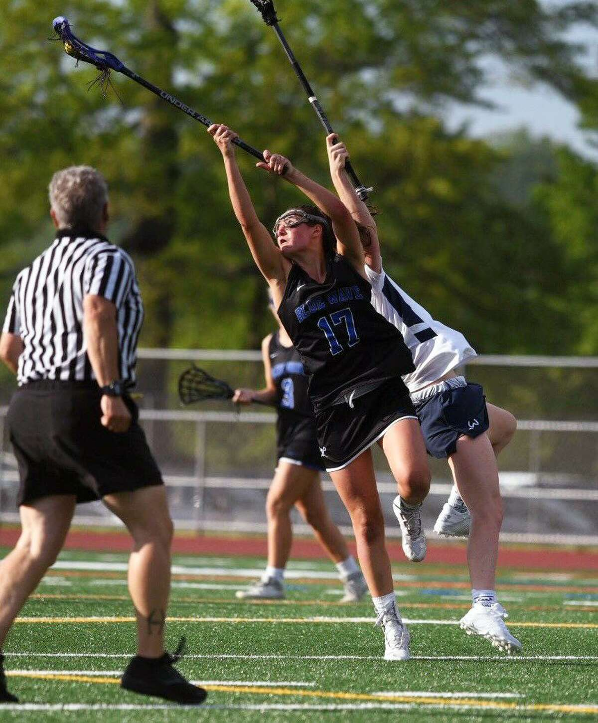 Darien's Sarah Jaques (17) takes to the air to grab a draw during the Wave's FCIAC girls lacrosse semifinal game against Wilton at Testa Field in Norwalk on Monday, May 20, 2019.