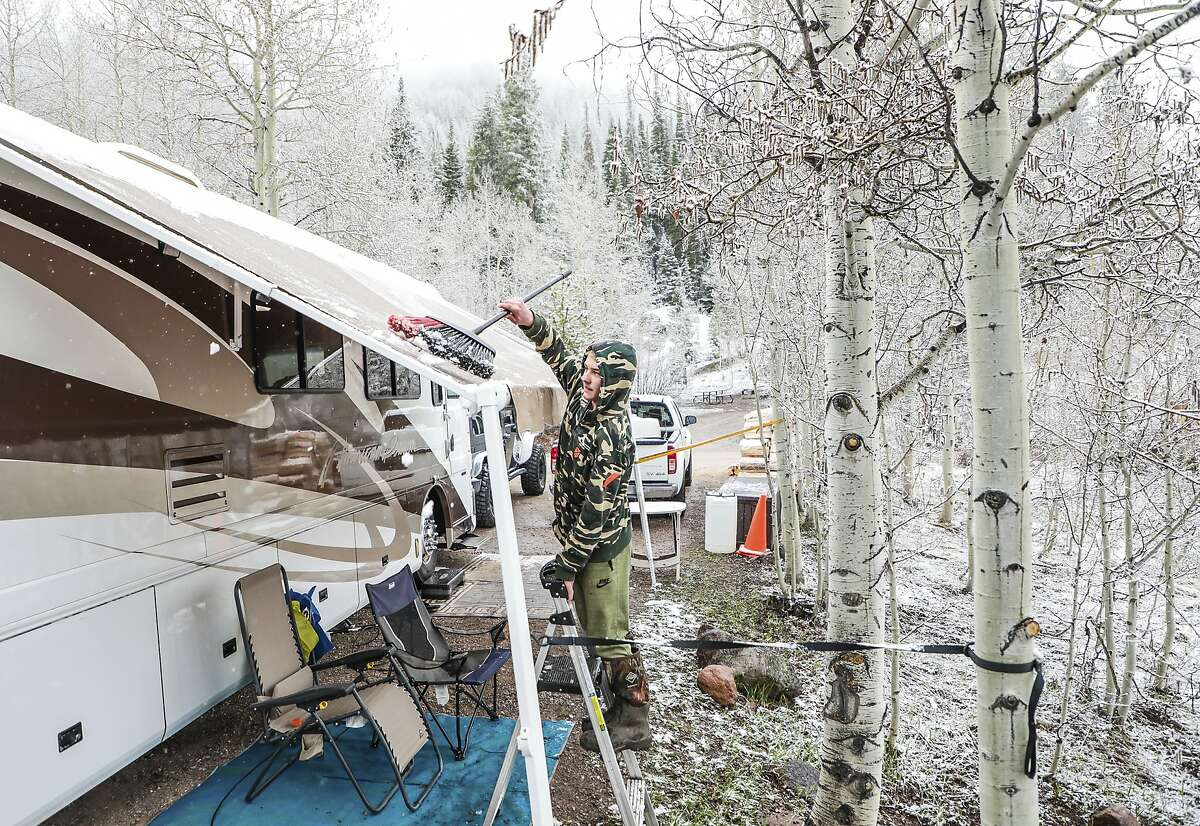 Dylan Totterdale, 14, clears the snow off the awning of their RV Monday, May 20, 2019 at the Gore Creek Campground in East Vail, Colo. The Totterdales are the hosts of the campground, and RV around the country fulltime. This year they said it's been a cold one at the site with all the snow. (Chris Dillmann/Vail Daily via AP)
