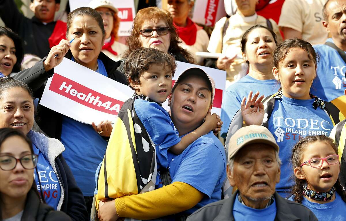 Oralia Sandoval, center, holds her son Benjamin, 6, as she participates in an Immigrants Day of Action rally May 20, 2019, in Sacramento.