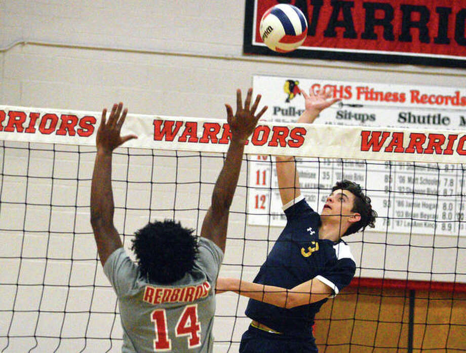 Father McGivney sophomore Darren Luchetti, right, goes up for a kill during Monday's first-round match against Alton in the Granite City Regional. Photo: Scott Marion/The Intelligencer