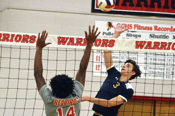 Father McGivney sophomore Darren Luchetti, right, goes up for a kill during Monday's first-round match against Alton in the Granite City Regional.
