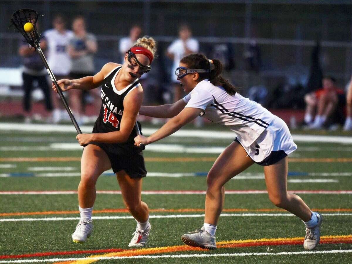 New Canaan's Campbell Connors (14) drives while Staples' Samantha Pacilio (8) defends during the FCIAC girls lacrosse semifinals at Norwalk's Testa Field in Monday, May 20, 2019.