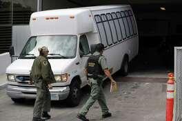 ARCHIVO - En esta foto de archivo del martes 19 de marzo de 2019, una camioneta que transporta a solicitantes de asilo desde la frontera es escoltada por personal de seguridad cuando llega a la corte de inmigración, en San Diego. El Cabildo de la Ciudad de Laredo votó por unanimidad el lunes para alentar a la administración de la ciudad a tomar las medidas necesarias para que una corte de inmigración este ubicada en el centro de Laredo.
