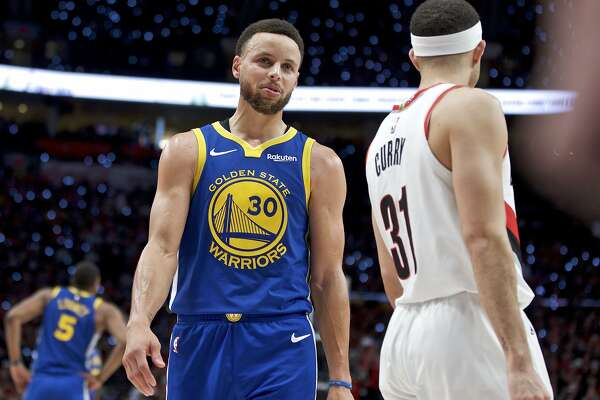 Golden State Warriors guard Stephen Curry, left, talks to Portland Trail Blazers guard Seth Curry during the second half of Game 3 of the NBA basketball playoffs Western Conference finals Saturday, May 18, 2019, in Portland, Ore. The Warriors won 110-99. (AP Photo/Craig Mitchelldyer)