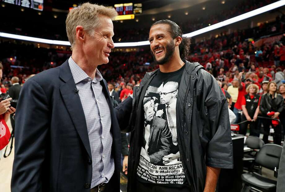 Golden State Warriors head coach Steve Kerr talks with former 49er quarterback Colin Kaepernick after the Warriors' 119-117 overtime playoff defeat of Portland on May 20. Photo: Scott Strazzante / The Chronicle