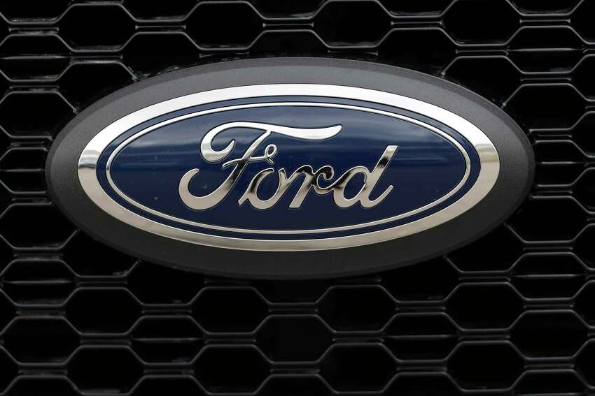 FILE- In this Feb. 17, 2019, file photo the company logo is displayed on the grille of an unsold 2019 F150 pickup truck at a Ford dealership in Broomfield, Colo. Ford is almost finished with a major global restructuring, and by the time it ends in August the automaker will have shed 7,000 white-collar jobs. The company said Monday, May 20 that the plan will save about $600 million per year by eliminating bureaucracy and increasing the number of workers reporting to each manager. (AP Photo/David Zalubowski, File)