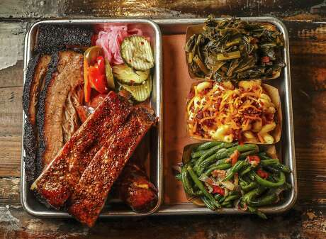 Three-meat tray with moist brisket, pork ribs, and jalapeño sausage served with sides of collard greens, green beans with tomatoes and onions, and mac and cheese with bacon and cheddar cheese, along with pickles, pickled onions and escabeche at Truth BBQ