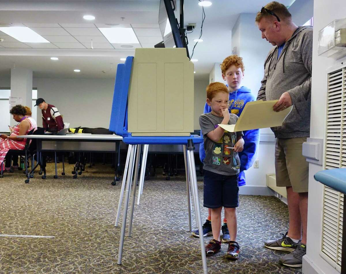 Ed Verhoff expalins to his sons, E.J., 11, and Liam, 7, about the ballot as he voted on the Albany School District budget at a polling site at Maria College on Tuesday, May 21, 2019, in Albany, N.Y. (Paul Buckowski/Times Union)