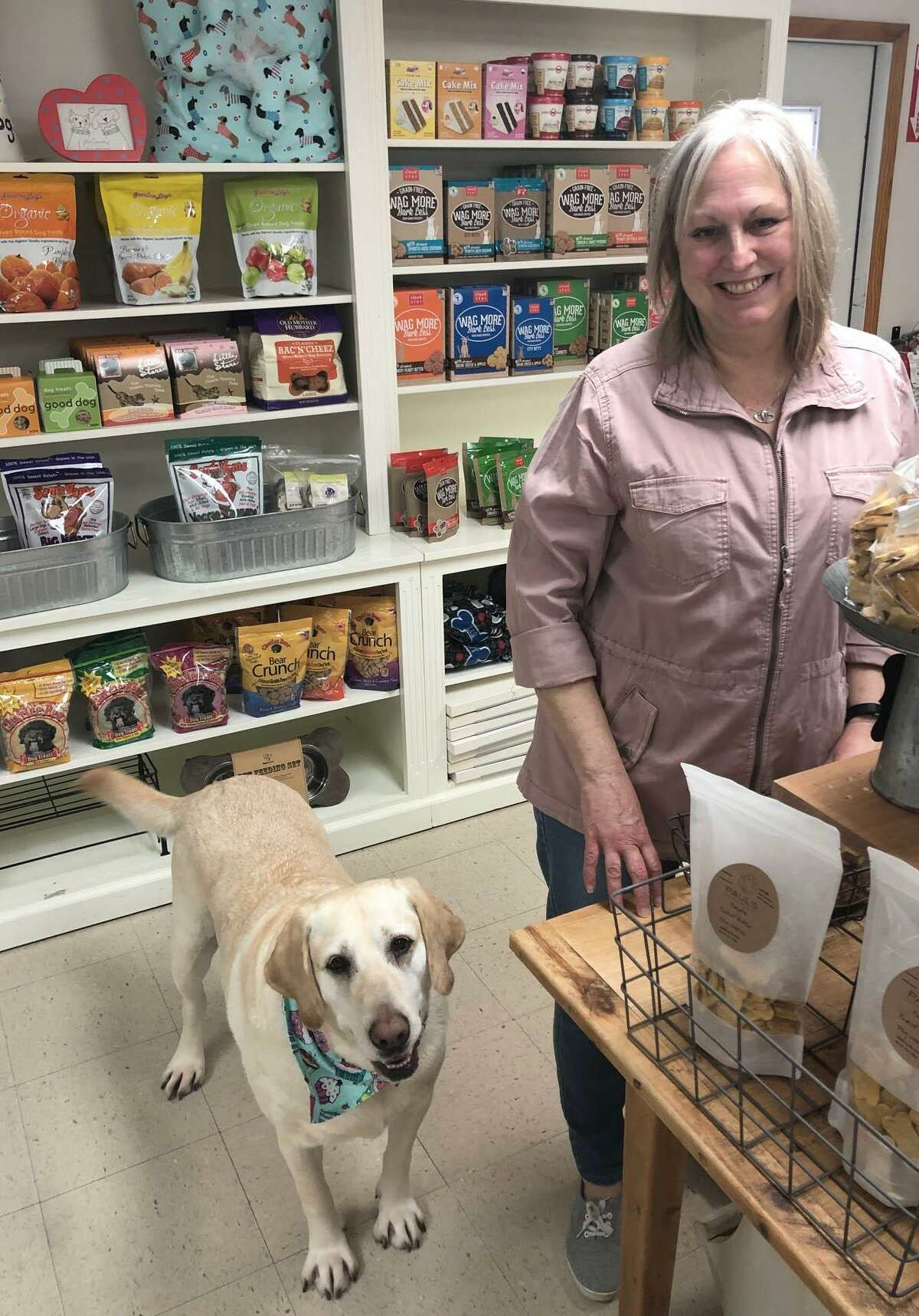 Debbie Bauman, owner of The Barkery Boo'tique in New Milford has moved the business from Bank Street to 92 Park Lane Road (Route 202). Bauman is shown above with her dog, Daisy, an 8-year-old Yellow Lab, who is the store's