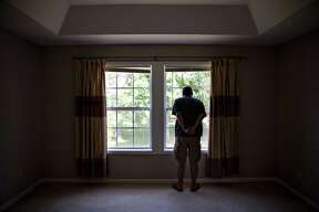 A prospective home buyer looks out the master bedroom window at a house for sale in Dunlap, Illinois, on Aug. 19, 2018. Photographer: Daniel Acker/Bloomberg