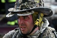 A Rensselaer firefighter takes a short break while battling a blaze that consumed a row house and damaged two others at 24 Broadway on Tuesday, May 21, 2019, in Rensselaer, N.Y. The fire was reported at about 9:30 a.m. (Will Waldron/Times Union)