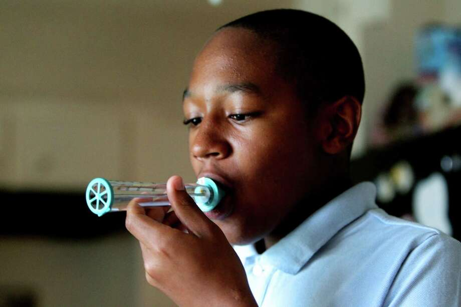 A 14-year-old uses a peak flow meter to test his lung capacity as he exhales to help manage his asthma. Photo: Gary Coronado / Houston Chronicle / © 2014 Houston Chronicle