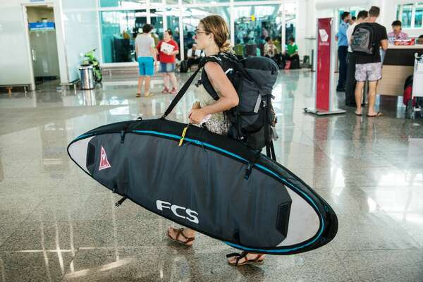 Foreign tourist carries surf boad as she arrive at Ngurah Rai international airport departure on July 13, 2015 in Denpasar, Bali, Indonesia. Bali's international airport reopened after being closed due to volcanic ash clouds from Maunt Raung, but Australia's main carriers to the holiday destinations are still not flying. (Photo by Agung Parameswara/Getty Images)