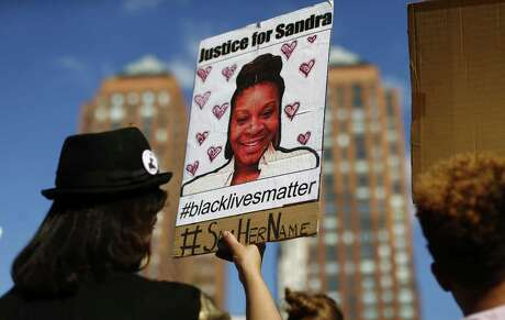 A woman holds a poster bearing the portrait of Sandra Bland, a 28-year-old black woman who died in a Texas jail cell on July 13th, at a rally in Union Square August 9, 2015 in New York. Newly released cellphone video from the arrest has raised new interest in the case, leading Democratic state Rep. Garnet Coleman to set a hearing on the matter in the County Affairs Committee on Friday. (Kena Betancur/AFP/Getty Images/TNS)
