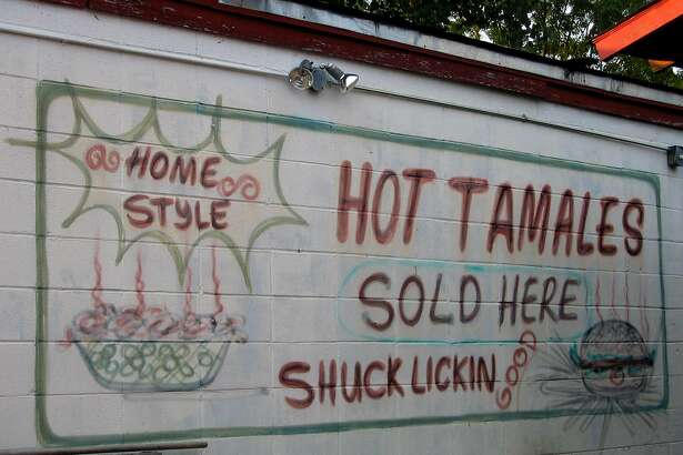 """Delta tamales. A sign on the side of Delta Fast Foods on U.S. 61 in Cleveland, Miss., promises tamales that are """"shuck lickin' good."""" Photo by Rod Davis, staff. July 2004."""