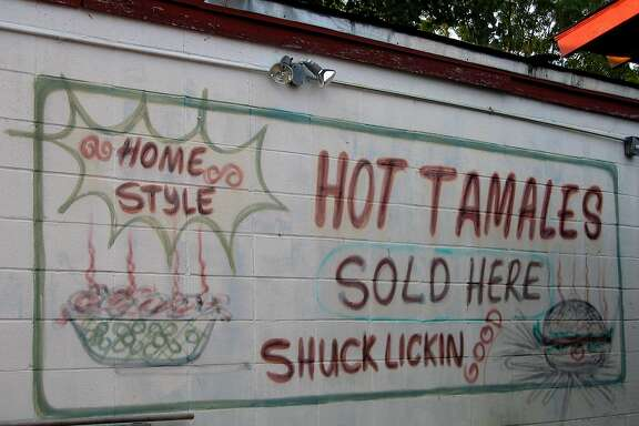 "Delta tamales. A sign on the side of Delta Fast Foods on U.S. 61 in Cleveland, Miss., promises tamales that are ""shuck lickin' good."" Photo by Rod Davis, staff. July 2004."