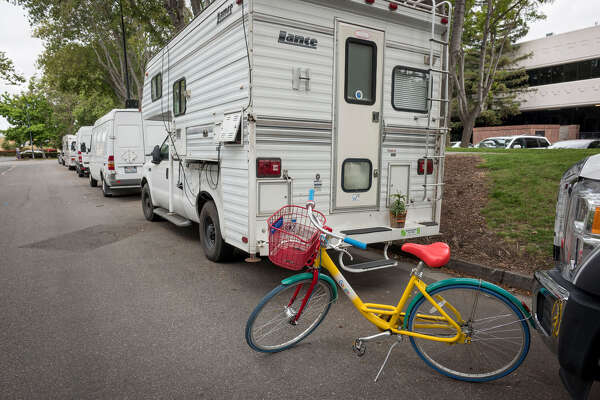 A Google bicycle stands behind a recreational vehicle parked on Landings Drive in Mountain View, Calif., on May 14, 2019.
